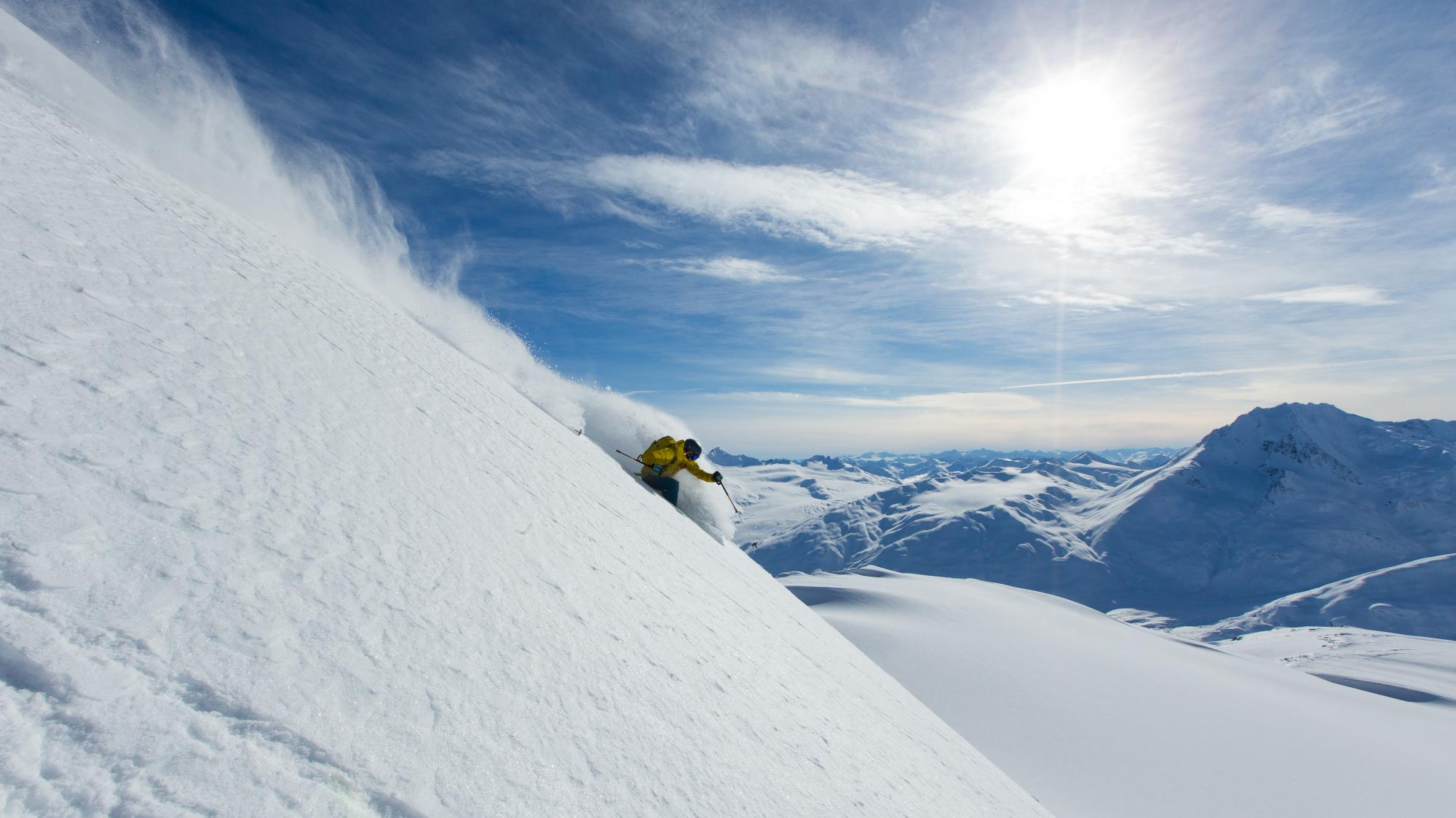 Skier on steep powder on a bluebird day
