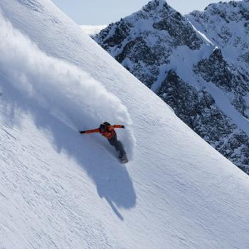rider in deep powder on steep slope